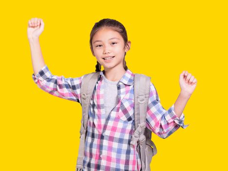 Happy student girl with school bag.Openning arms.Isolated on yellow background.