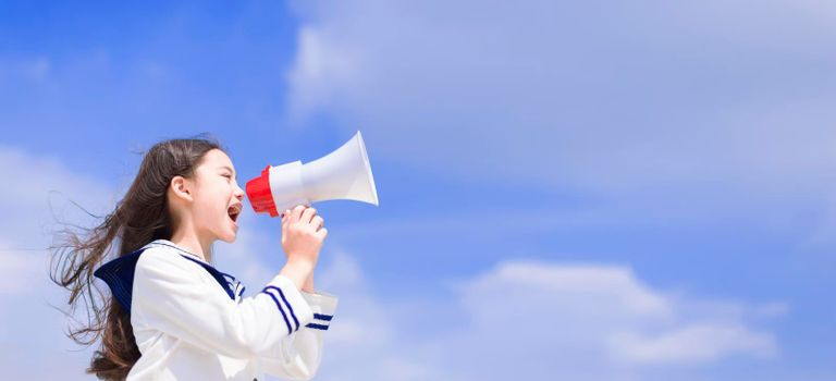 School girl shouting and announcing with megaphone