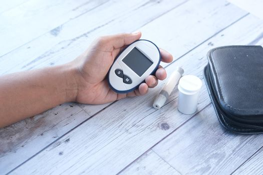 Rear view of hand hold a diabetic measurement tools on table