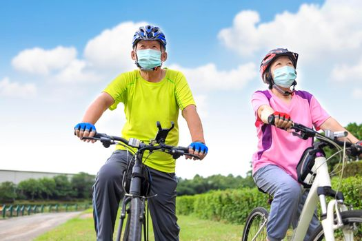 Asian Senior couple  wearing medical mask and riding bicycle in the park