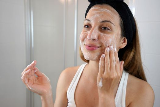 Young Skin Care Routine. Girl washing face foaming soap scrubbing skin. Face wash exfoliation scrub soap woman washing scrubbing with skincare cleansing product.