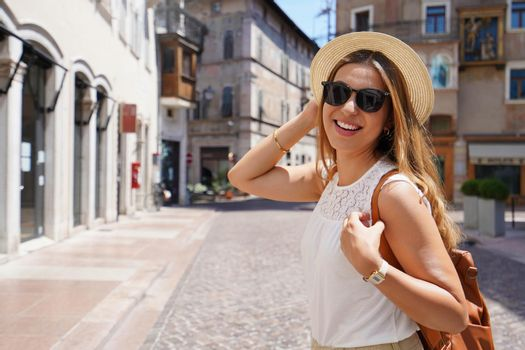 Dynamic cheerful woman on cultural destination in Europe. Fashion girl looking at camera on her touristic adventure. Copy space.