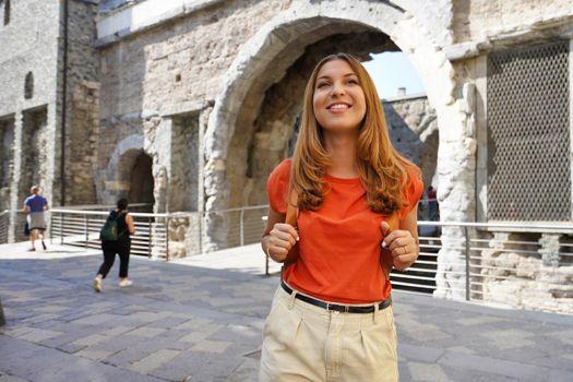 Cultural tourism in Italy. Traveler girl passes through the Porta Praetoria gate in Aosta city, northern Italy.