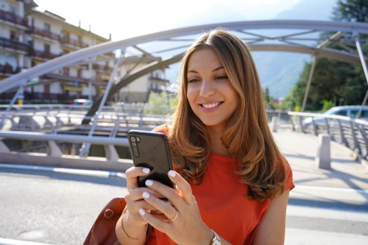 Close up of smiling woman wearing orange blouse texting on mobile phone in sustainable city