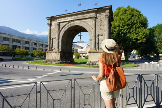 Tourism in Italy. Back view of tourist girl looking the Arch of Augustus in Aosta, Italy.
