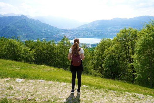 Female hiker standing on the trail and looks with satisfaction from the top of mountain the lake
