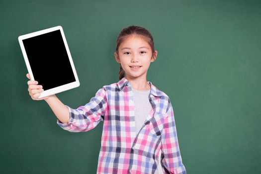 Happy student girl showing tablet. Isolated on green chalkboard background.