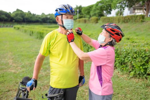 Senior couple  wearing medical mask and riding bicycle in the park