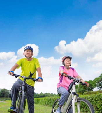 Asian healthy senior couple exercising with bicycles