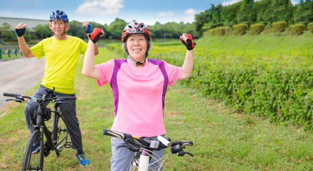Happy Asian healthy senior couple exercising with bicycles