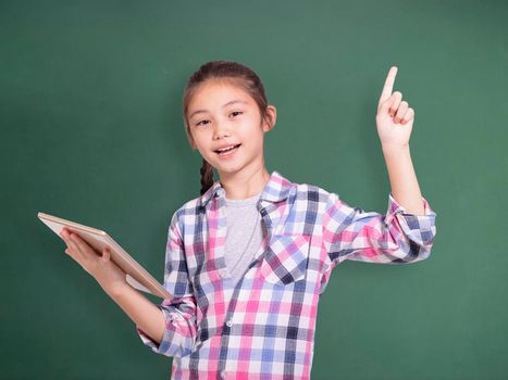 Happy student girl holding tablet and pointing upside.Isolated on green chalkboard background.