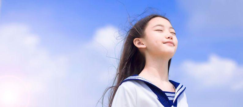 Beautiful student girl enjoying summer breeze , smiling with eyes closed