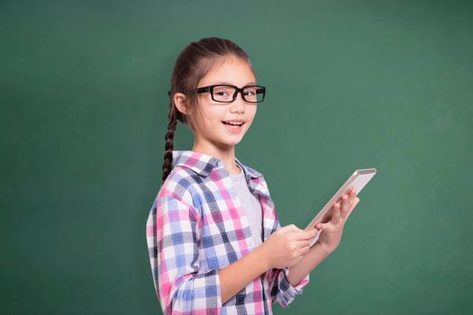Happy student girl with glasses using tablet.Isolated on green chalkboard background.