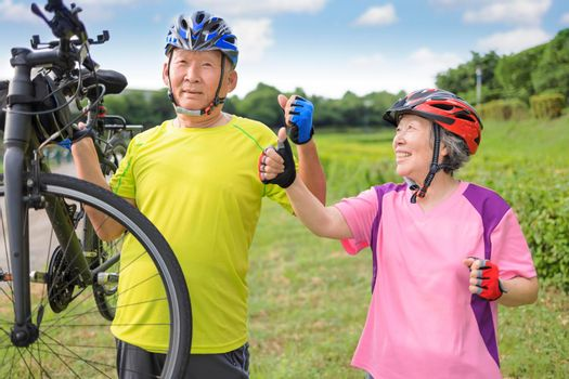 Happy healthy senior couple exercising with bicycles and showing thumbs up