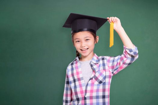 Happy student girl wearing graduation cap.Isolated on green chalkboard background.