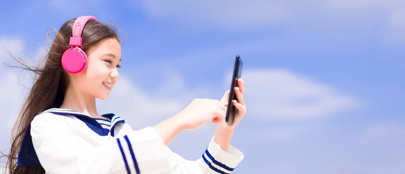 Beautiful student girl  listening music in headphones and watching the mobile phone