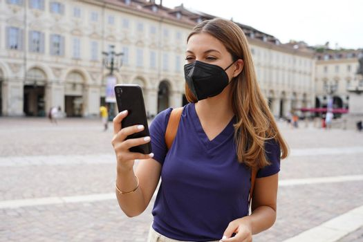 Portrait of student girl with black protective mask FFP2 KN95 using smart phone outdoor