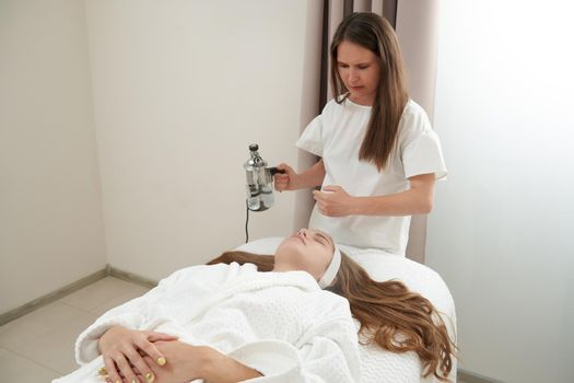 The procedure of steaming the skin of the face of a young woman before cleaning the skin in a cosmetology salon
