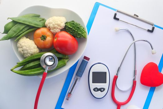 diabetic measurement tools and fresh vegetable on table