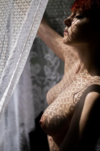 Sexy nude woman in shadow from openwork fabric outdoors in summer.