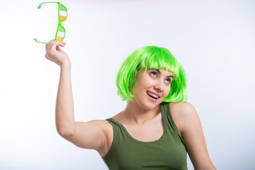 Cheerful young woman in green wig and funny glasses celebrating st patrick's day on a white background