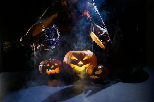Witch casts a spell on a steaming pumpkin in the dark on Halloween