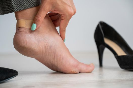 A woman in black shoes puts a plaster on a corn