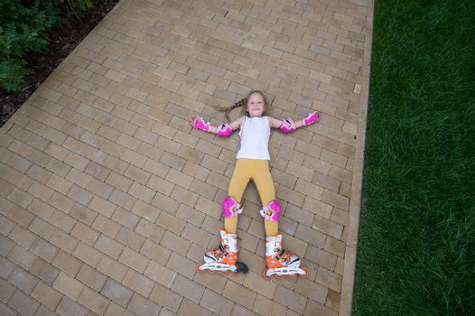 Little girl learns to roller skate and falls. View from above
