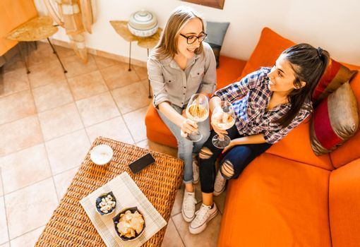 Couple of young women friends drinking at home sitting at orange sofa celebrating with champagne or white wine. Girls using alcohol to having fun taking aperitif in living room instead of study lesson
