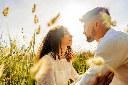 Romantic scene of multiracial passionate young couple in love looking in eyes each other among high grass vegetation at sunset or dawn with sun backlit effect Romance dream shot of lovers in nature