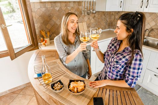 Couple of young women friends drinking at home in the kitchen celebrating with champagne or white wine Two girls using alcohol to having fun in the day taking aperitif instead of study lesson