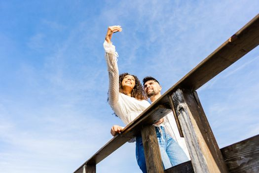 Unusual low angle view shot of multiracial couple on a wooden beach bridge taking a selfie in vacation at sea ocean resort. Large sky copy space ideal for banner or ads. Hispanic girl using smartphone