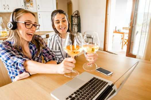 Two happy young women at home sitting at table looking laptop toasting with champagne or white wine glasses. New normal celebration online due to social distancing and video conferencing technology