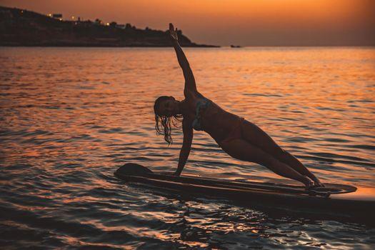 Woman Doing SUP Balance Yoga on Sunset