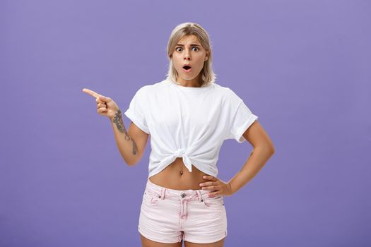 Girl being unhappy with unfair thing happened. Shocked displeased complaining, confused woman with tanned skin blond hair and tattoos opening mouth and frowning from jealousy or regret pointing left