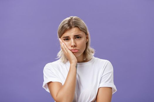 Waist-up shot of unhappy miserable and sad cute blonde female in white casual t-shirt pursing lips leaning face on palm and frowning from disappointement and regret over purple background