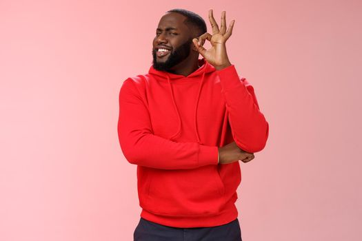 Attractive satisfied happy charismatic handsome male black customer very impressed recommend good quality service show okay ok perfection gesture smiling happily, pink background