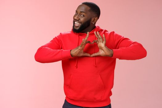 Someone love ya. Portrait enthusiastic creative cute black boyfriend wearing red hoodie show heart sign smiling broadly confessing love sympathy look passionate, express romance pink background