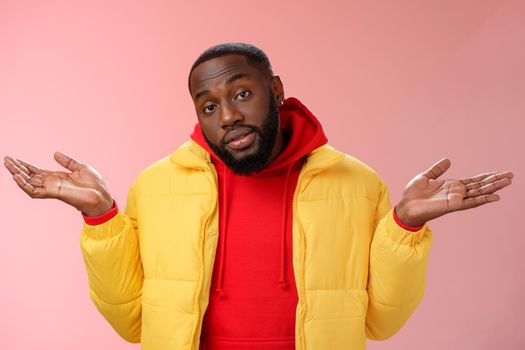 Indoor shot black bearded 25s guy shrugging hands raised sideways dismay clueless gesture have no idea standing careless questioned unaware what happened unbothered pink background