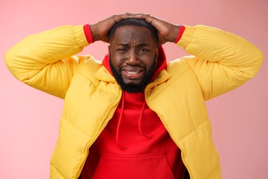 Upset unhappy african-american male entrepreneur lose money feel regret sadness grimacing painful heartbreaking feelings, holding hands head depressed devastated, standing pink background