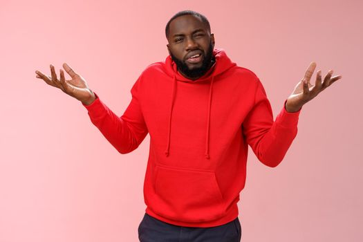 Bothered pissed african american bearded boyfriend in red hoodie arguing standing questioned bothered stupid accusations shrugging raise hands dismay cringing perplexed, pink background