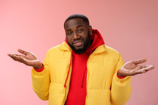 Close-up clueless unaware handsome stylish african-american bearded man in yellow jacket shrugging hands spread sideways dismay cannot understant anything standing perplexed, pink background