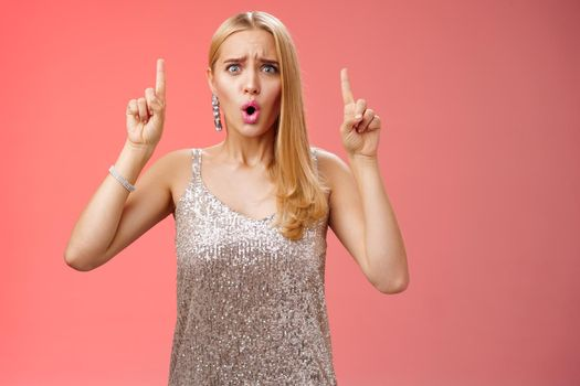 Upset gloomy complaining blond whining girl in silver stylish luxurious dress frowning cringing unhappy pointing up regret jealous tell boyfriend sale over, standing depressed sad red background