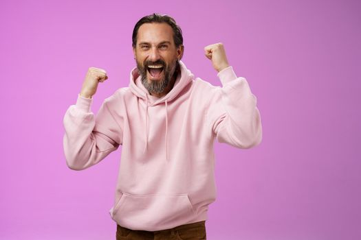 Cheerful supportive manly mature adult bearded guy fan yelling raising clenched fists triumphing team scored goal celebrating standing pleased shouting achieving success, posing purple background