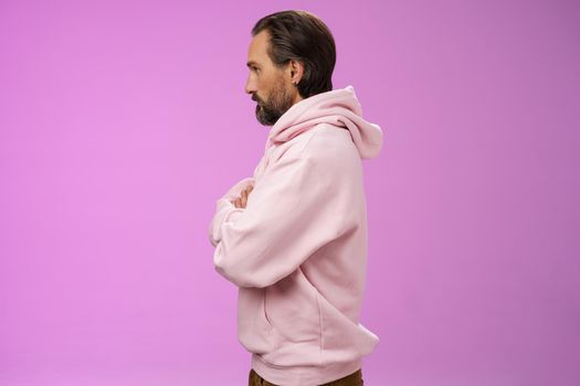 Profile shot serious-looking confident closed defensive adult bearded 40s guy cross arms chest look left impatient irritated standing purple background bothered waiting queue concerned