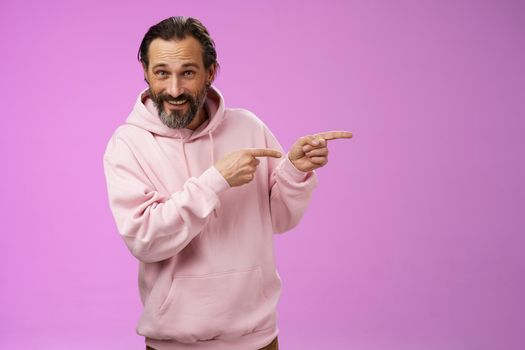 Sassy confident good-looking macho man 50s in pink hoodie smiling broadly inviting join pointing right showing interesting amusing place hang out welcoming take look, standing purple background
