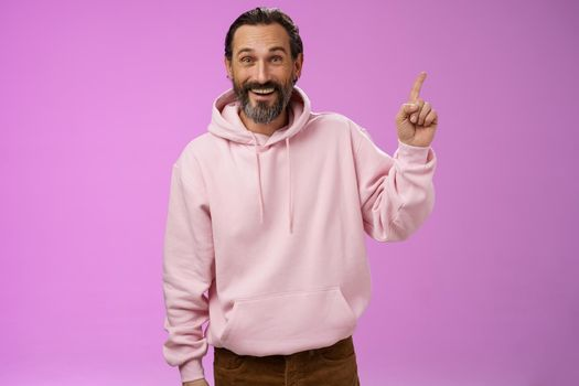 Handsome excited mature 40s bearded man wrinkles grey hair laughing happily acting immature having fun amusing vacation trip pointing up astonished smiling impressed surprised, purple background