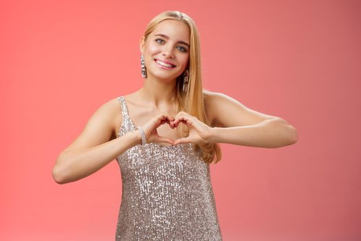 Romantic passionate charming lovely blond glamour woman in silver dress brilliants show heart love gesture express sympathy passion, adore relationship smiling delighted, standing red background