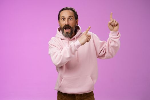 Impressed shocked exctied cool hipster mature 50s man bearded grey hair in pink hoodie retelling incredible story pointing up index fingers widen eyes surprised thrilled awesome advertisement