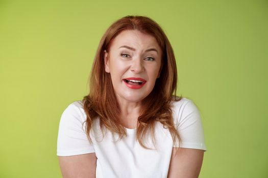Tender redhead cheerful middle-aged mother sighing happiness temptation smiling delighted look alluring fascinated camera check out cute lovely scene melting heartwarming moment green background